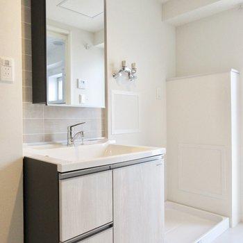 洗面台はキッチンと同じタイル張り。隣に洗濯機置き場があって、動線◎ですよ。
