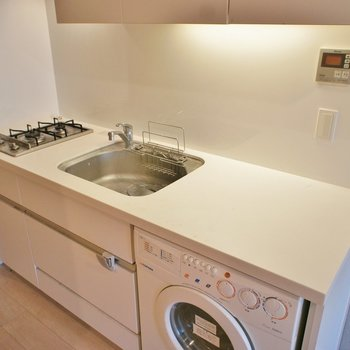 キッチンも広い。ドラム式洗濯機もある ※写真は4階の同間取り別部屋のものです。