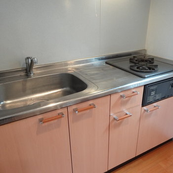 キッチンはオレンジ色。2口ガスコンロで、1人暮らしには大きめになってます。自炊がんばっちゃう?※写真は同間取り別部屋のものです