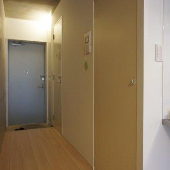 廊下に洗濯機、サニタリーの扉。