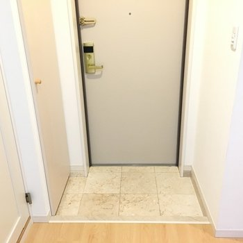 玄関はコンパクト。※写真は6階の反転間取り別部屋のものです