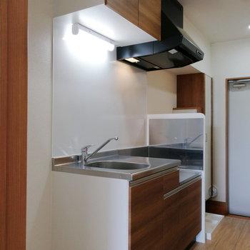 キッチンはブラウンで。※写真は同階の反転間取り別部屋のものです