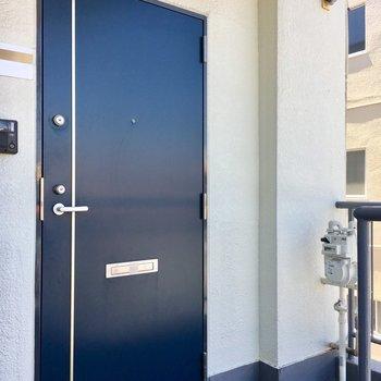 爽やかなネイビーブルーの玄関ドア。お隣さんとは離れているのでプライベート感があります。