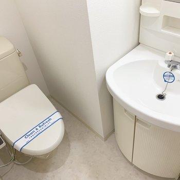 洗面脱衣所兼トイレ。洗面化粧台のフォルムが素敵。(※写真は13階の同間取り別部屋のものです)