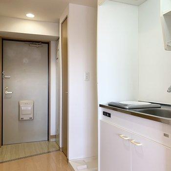 手前からキッチン・洗濯機置場・クローゼット。奥に給湯器と玄関。(※写真は13階の同間取り別部屋のものです)