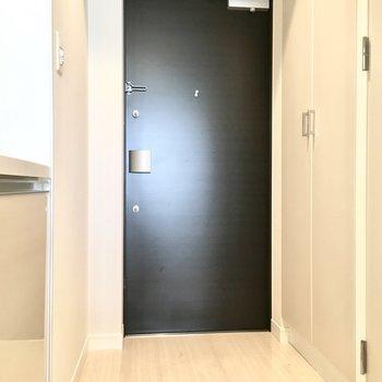 白い空間に黒のドアがキリッとしめる玄関。