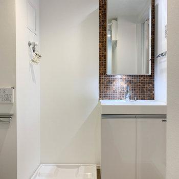 廊下の扉を開けると独立洗面台と洗濯機置き場が現れます。