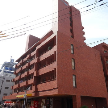 赤いしっかりとした建物。1階にはお店が。