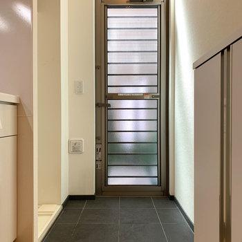 玄関部分はフラットな作りです。玄関横に洗濯機置き場があります。