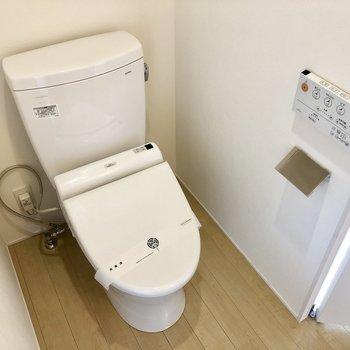 トイレは壁にボタンがあってかっこいい※写真は6階の反転間取り別部屋のものです