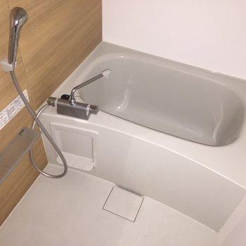 お風呂には木目のアクセントクロスが。※写真は通電前・2階の反転取り別部屋のものです