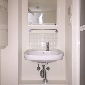 洗面台は白のタイルがかわいい。※写真は通電前・2階の反転取り別部屋のものです