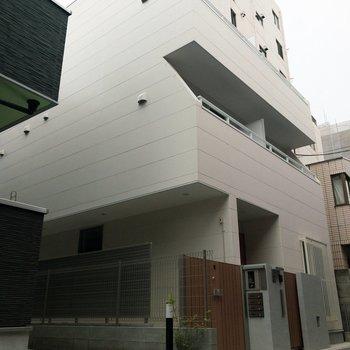 端正な白亜の外壁とオートロックの玄関です