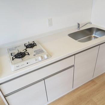 真っ白のキッチンは2口コンロのシステムキッチン。