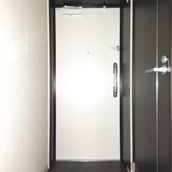 モノトーンがクールな玄関。※写真は通電前のものです・フラッシュを使用しています