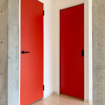 【洋室7.8帖】赤い扉が二つ。左がクローゼット。右が水回りです。