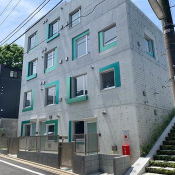 緑のアクセント効いた、クールな外観のマンションです。
