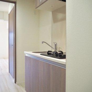 主張しすぎないウッド調のキッチン※写真は7階の同間取り別部屋のものです