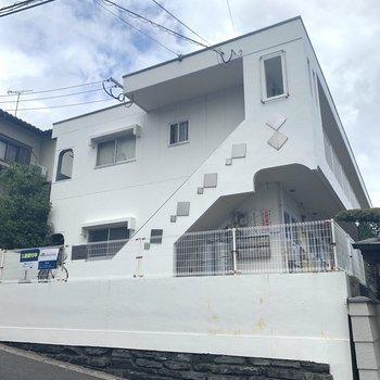 白外装に、カラフルなドア達がステキな2階建てアパート。