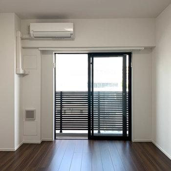 白とウッドの空間。窓から見えるベランダの柵も、シックでおしゃれな色合い。※写真は4階の反転間取り別部屋のものです