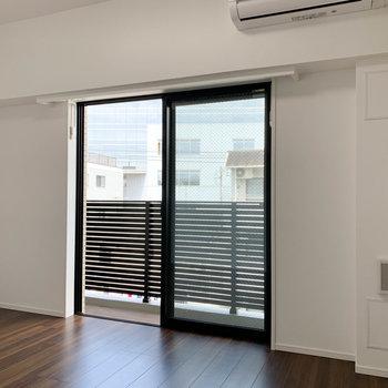 白とウッドの空間。窓から見えるベランダの柵も、シックでおしゃれな色合い。