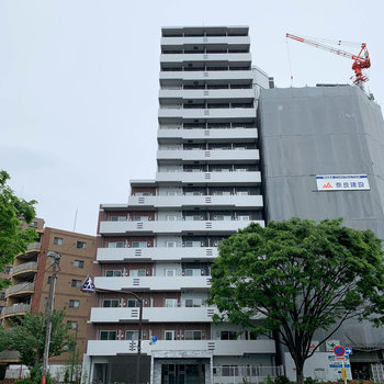 交差点沿いにある15階建てのマンションです。