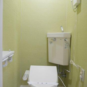 ライトグリーンの壁紙でかわいいトイレ