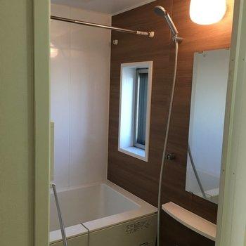 茶色い壁のお風呂、鏡と窓が!※写真は8階の同間取り別部屋のものです