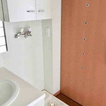 洗面台の隣に洗濯機置き場。上に収納も。