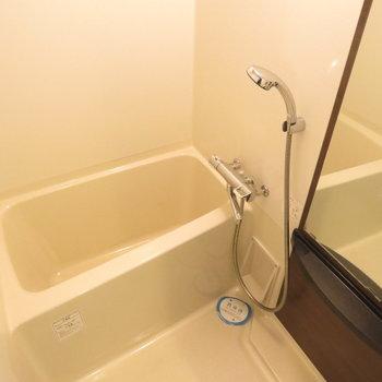 シャワーヘッドの大きなお風呂※写真は14階の反転間取り別部屋のものです。