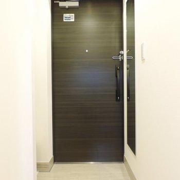 玄関はシックな色合い※写真は2階の同間取り別部屋のものです