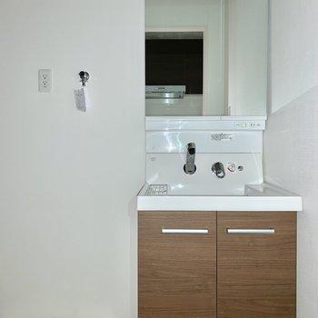 洗面台は落ち着いたデザイン。洗濯機は横ですね※写真は通電前のものです