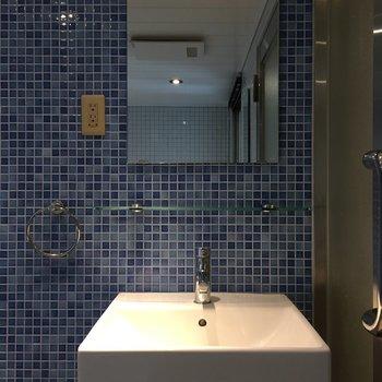 青のタイルで洗面台の白が映えますね。※写真は5階の同間取り別部屋のものです