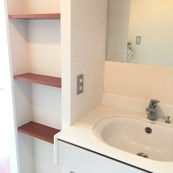 独立洗面台。棚板のブラウンにはちいさなグリーンを添えたい。(※写真は13階の同間取り別部屋のものです)