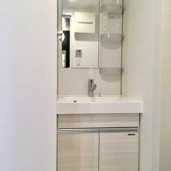 サニタリー入って左に洗面台。※写真は2階の同間取り別部屋のものです