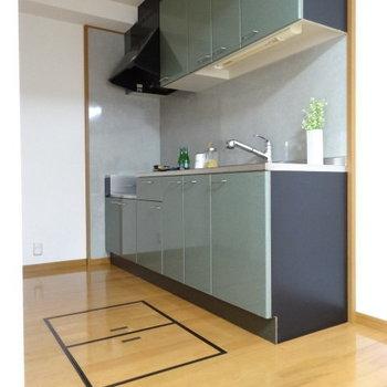 モスグリーンのキッチンが素敵。(※写真は別棟1階の反転間取り、モデルルームのものです)