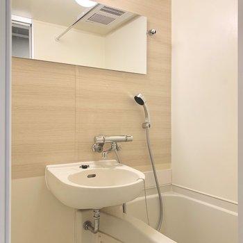 木目のシートと横長の鏡がお洒落!サーモ水栓とハンガーポールもついて便利になりました。