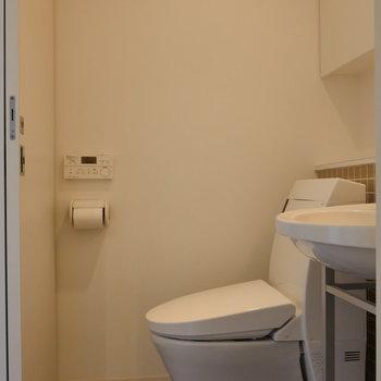 お隣にトイレ。上部に収納棚もありますね。