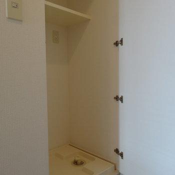 扉の向こうに洗濯機※写真は12階の反転間取り別部屋のものです