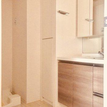 洗面台。奥には室内洗濯機置場※写真は4階の同間取り別部屋のものです