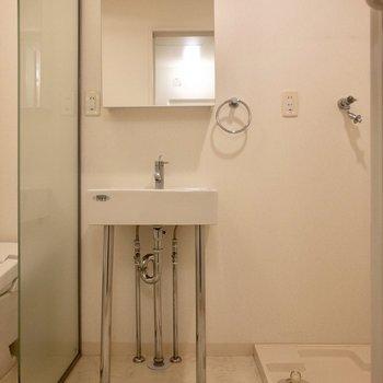 ミニマムなデザインの洗面台。横には洗濯機置場。※ 写真は前回募集時のものです