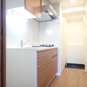 キッチンは周囲は木目調。※写真は7階の同間取り別部屋のものです