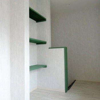 階段横にはグリーンのオープン収納。白に映える!