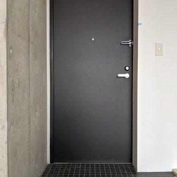 下階へ戻って玄関です。シックなドアとタイルがカッコイイ。(※写真は前回募集時の清掃前のものです)