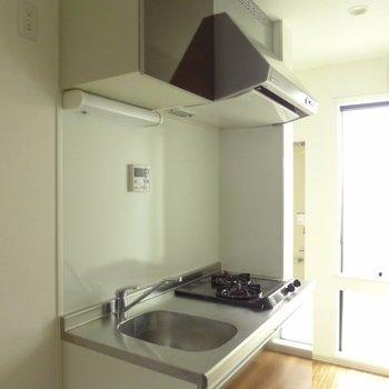 キッチンはコンパクトながら2口※写真は1階の反転間取り別部屋のものです