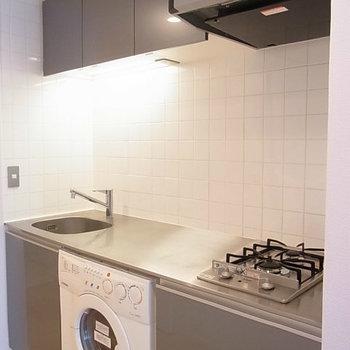 ドラム式洗濯機付のシステムキッチン※写真は11階の反転間取り別部屋のものです