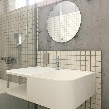 真っ白な洗面台にはまーるいミラー。(※写真は3階の同間取り別部屋のものです)