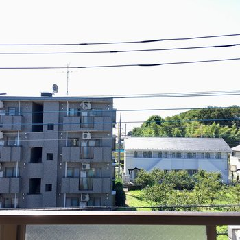 畑が見えますよ。奥に黄色い電車が走っています。(西武拝島線です)