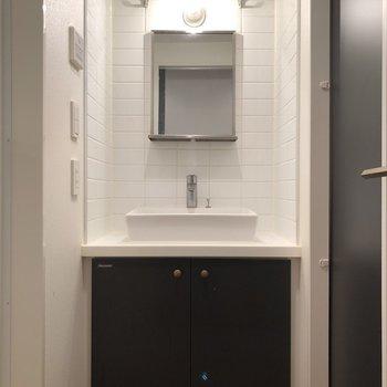 廊下にあるドアを開けると正面に洗面台があります。上部にある金網の収納棚がオシャレ…!※写真は3階の同間取り別部屋のものです