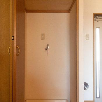 洗濯機置場は玄関脇の扉の中に。